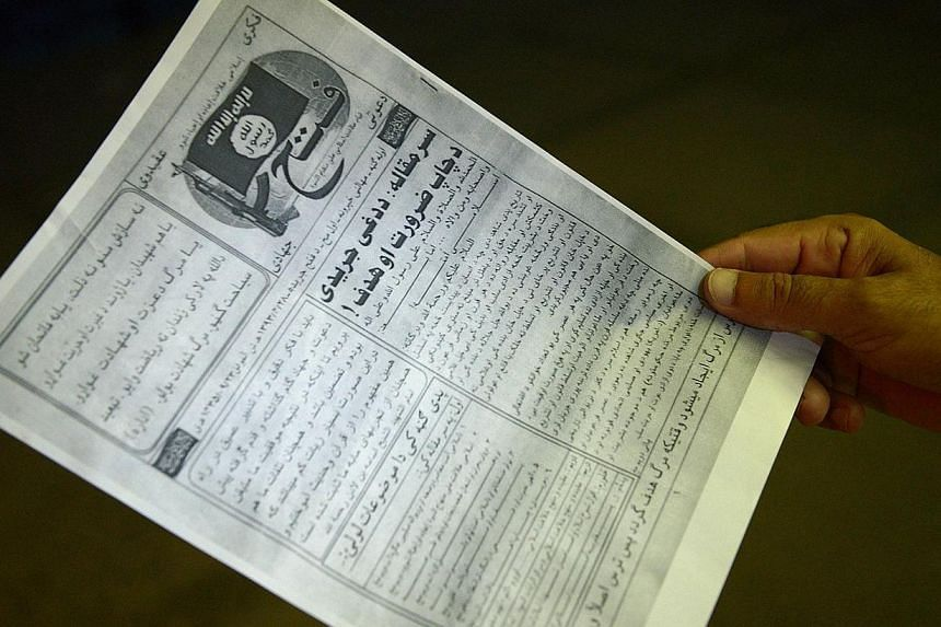 """A Pakistani man reads a pamphlet, allegedly distributed by the Islamic State (IS), in the northwestern Pakistani city of Peshawar on Sept 5, 2014.The UN Security Council plans to demand countries """"prevent and suppress"""" the recruitment and trave"""