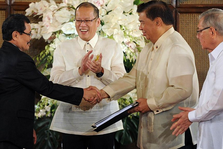 Mohager Iqbal (left), chief peace negotiator of the Moro Islamic Liberation Front (MILF), hands over the draft of the Bangsamoro basic law to Senate President Franklin Drilon (second right) at the Malignancy Palace in Manila on Sept 10, 2014 as Phili