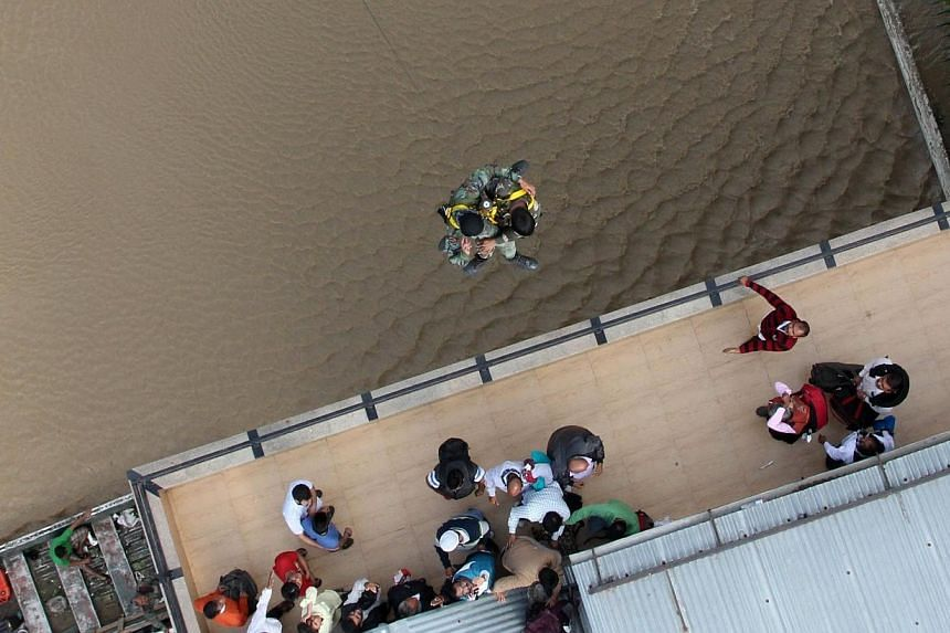 Indian Air Force personnel use a winch to reach residents stranded on a rooftop during rescue and relief efforts following flooding in Srinagar, Kashmir, in a photo released on Sept 10, 2014.Social media is playing a key role in linking up fami