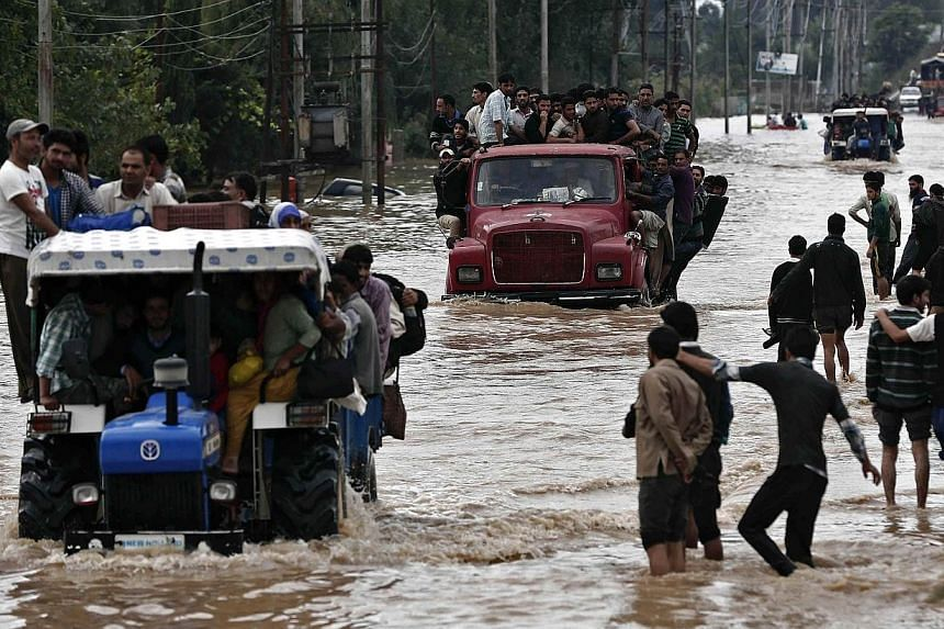 Vehicles evacuating Kashmiri flood victims to higher grounds travel through a flooded street in Srinagar on Sept 9, 2014. Flood waters started receding in Indian Kashmir on Wednesday, Sept 10, giving rescue teams a chance to reach tens of thousa