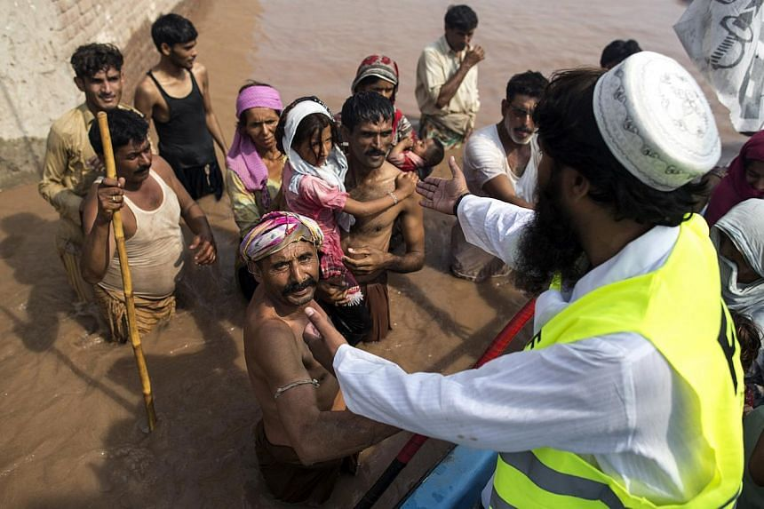 Flood victims wait to be evacuated by boat from their flooded house following heavy rain in Jhang, Punjab province, on Sept 10, 2014.Anger mounted on Wednesday over the slow pace of rescue operations in Indian Kashmir as the authorities said th