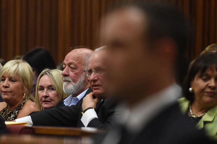 The mother of victim Reeva Steenkamp, June (second from left), seated next to her husband Barry (third from right), looks at Oscar Pistorius (foreground) in court on Sept 11, 2014. -- PHOTO: AFP