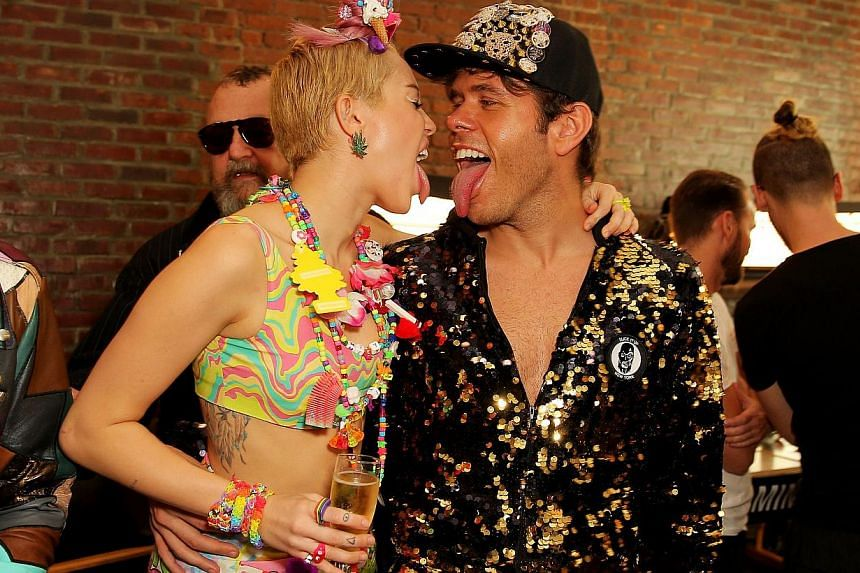 Miley Cyrus (left) and Perez Hilton pose baskstage at Jeremy Scott fashion show during MADE Fashion Week Spring 2015 at Milk Studios in New York City on Sept 10, 2014. -- PHOTO: AFP