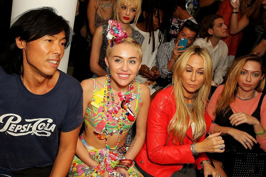 (From left) Stephen Gan, Miley Cyrus, Tish Cyrus and Brandi Cyrus attend Jeremy Scott fashion show during MADE Fashion Week Spring 2015 at Milk Studios in New York City on Sept 10, 2014. -- PHOTO: AFP
