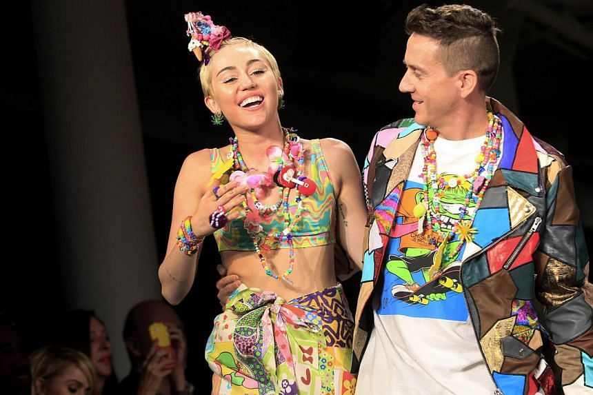 Miley Cyrus and designer Jeremy Scott walk the runway during his Spring/Summer 2015 collection at York Fashion Week in New York City Sept 10, 2014. -- PHOTO: AFP