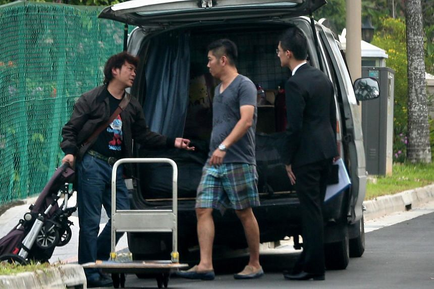 Mr Yang Yin (left) made his first public appearance yesterday when he turned up at the Gerald Crescent bungalow to retrieve his belongings. With him are his lawyer (right) and the driver of the van used to transport the items. -- ST PHOTO: NEO XIAOBI