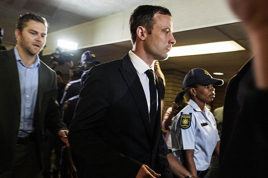 """""""Blade Runner"""" Oscar Pistorius (centre) arrived in court on Thursday to face judgment over the death of his glamorous lover, with the Paralympian facing a possible life sentence if found guilty of murder. -- PHOTO: AFP"""