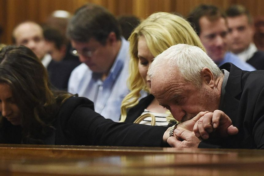 Oscar Pistorius' father Henke Pistorius (right) kisses the hand of his daughter Aimee Pistorius (left) at the North Gauteng High Court in Pretoria on Sept 11, 2014. -- PHOTO: REUTERS