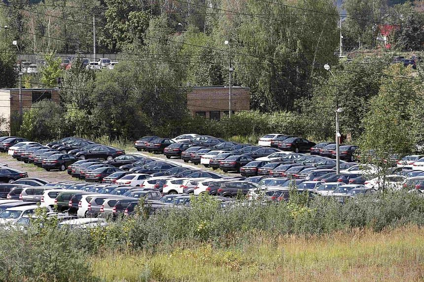 Cars, produced by foreign automobile-makers, are seen at a parking of a dealership on the outskirts of Moscow on Aug 18, 2014. -- PHOTO: REUTERS