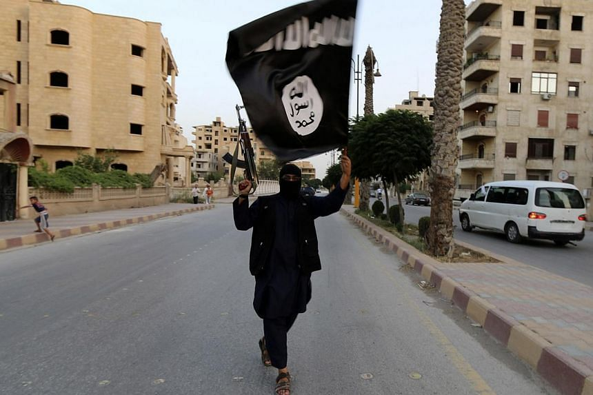 A member loyal to the Islamic State in Iraq and the Levant (ISIL) waves an ISIL flag in Raqqa, Syria in this file photograph. According to reports from Malaysia, a Penang-born man has taken his Singaporean wife and two children to Syria to join the j