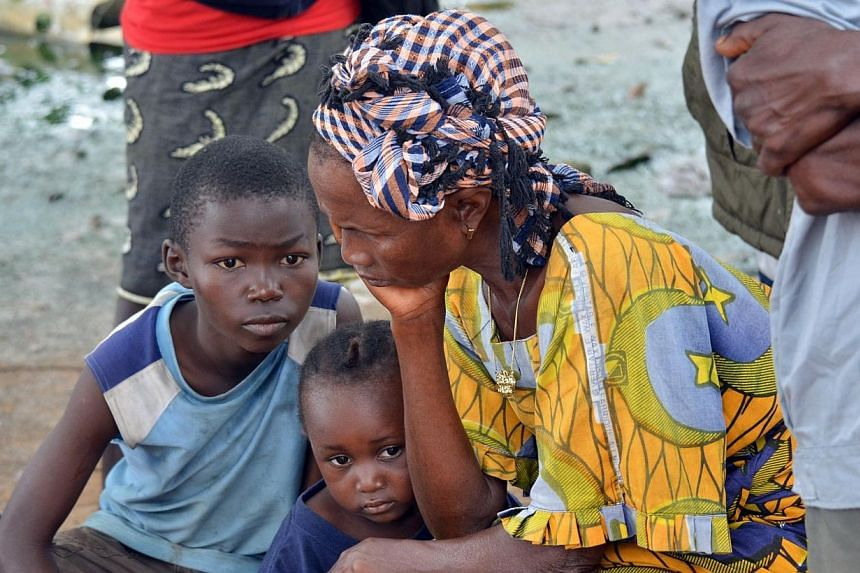 A woman and her kids mourn the death of a family member on Sept 10, 2014 in a district of Monrovia. -- PHOTO: AFP