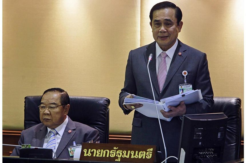 Thailand's Prime Minister Prayuth Chan-ocha (right) reads out his government's policy, as Deputy Prime Minister and Defence Minister Prawit Wongsuwan listens, at the Parliament in Bangkok on Sept 12, 2014.-- PHOTO: REUTERS