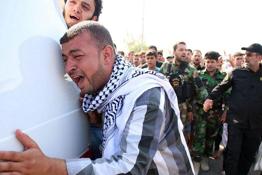 Iraqi mourners at the funeral of members of the Shi'ite militia Saraya al-Salam (Peace Brigade) who died fighting alongside government forces against ISIS fighters, in the southern city of Basra on Sept 4. The writer says the Iraqi tragedy makes him