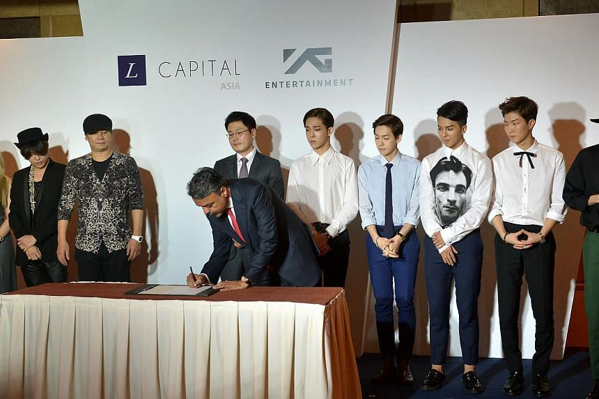 (From left) CL of K-pop girl group 2NE1, G-Dragon, YG Entertainment founder and chairman Yang Hyun Suk, YG Entertainment CEO Yang Min Suk and five-man boyband Winner watch on as L Capital Asia managing partner Ravi Thakran signs the investment agreem