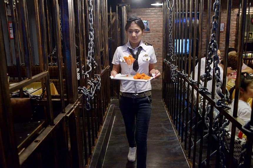 This picture taken on Sept 9, 2014 shows a waitress carrying food to customers at a prison themed restaurant in Tianjin. -- PHOTO: AFP