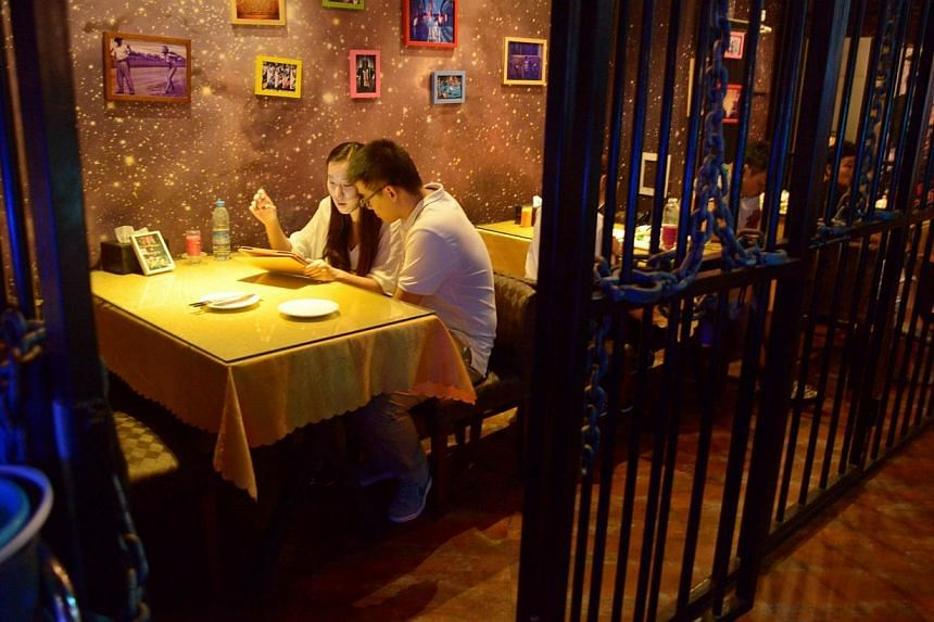 This picture taken on Sept 9, 2014 shows a couple preparing to have dinner at a prison themed restaurant in Tianjin.-- PHOTO: AFP