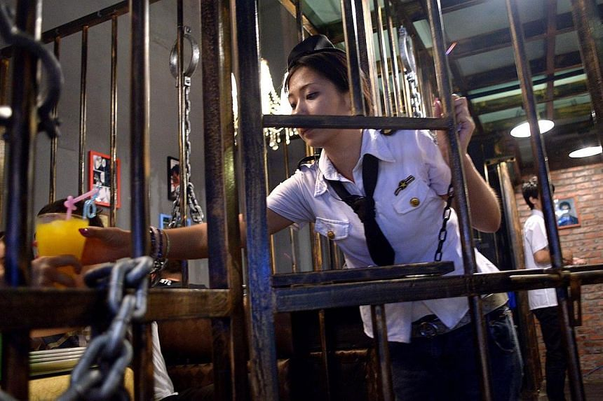 This picture taken on Sept 9, 2014 shows a waitress handing over a cup of drink to a customer at a prison themed restaurant in Tianjin. -- PHOTO: AFP