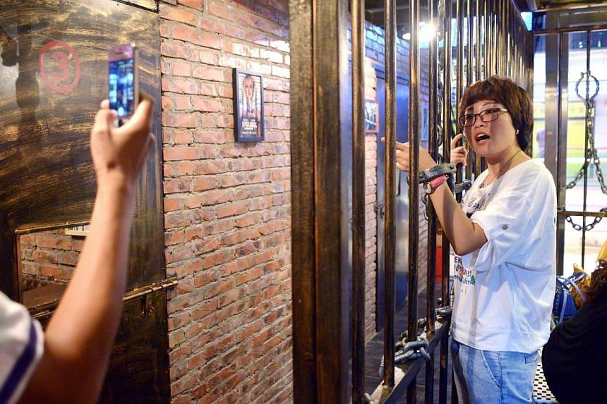 This picture taken on Sept 9, 2014 shows a family taking a photo before their dinner at a prison themed restaurant in Tianjin.-- PHOTO: AFP