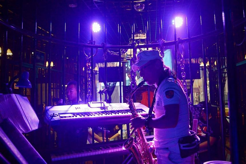 This picture taken on Sept 9, 2014 shows a musician performing at a prison themed restaurant in Tianjin. -- PHOTO: AFP