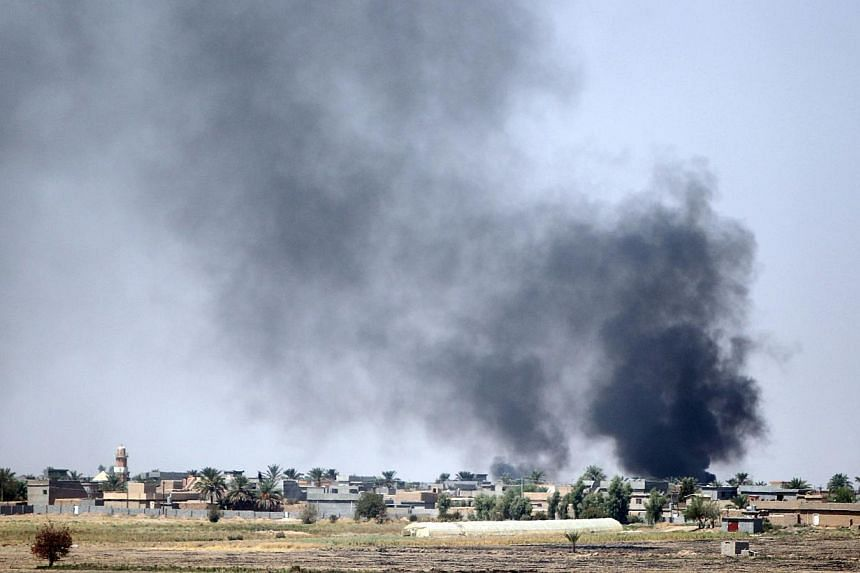 Smoke rises in the distance after Iraqi forces fired a mortar towards the village of Yakanja controlled by Islamic State in Iraq and Syria (ISIS) militants during heavy clashes near Tuz Khurmatu in Salaheddin province, about 88km south of Kirkuk, on