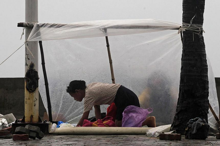 A woman shields herself with a plastic sheet from the rain brought on by Typhoon Kalmaegi, also called Luis, on the street at a bay in Manila on Sunday, Sept 14, 2014. The typhoon slammed into the rice-producing Philippine northern region on Sun
