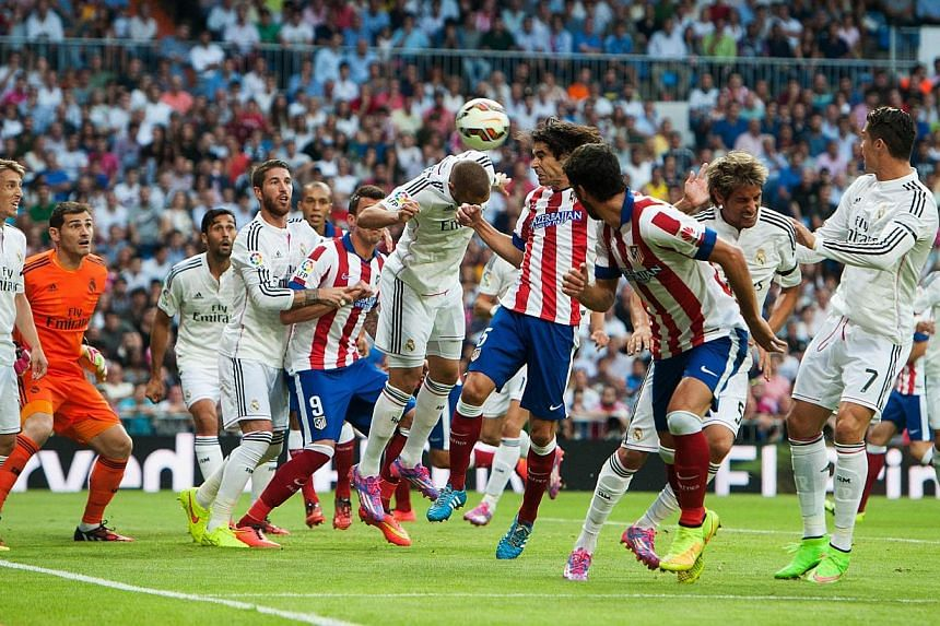Atletico Madrid's Portuguese midfielder Tiago Mendes (centre) heads the ball to score during the Spanish league football match against Real Madrid CF at the Santiago Bernabeu stadium in Madrid on Sept 13, 2014. -- PHOTO: AFP