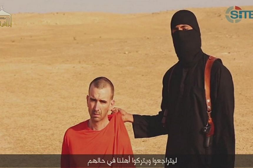 A video purportedly showing threats being made to a man Islamic State (IS) named as David Haines by a masked IS fighter in an unknown location in this still image from video released by Islamic State on Sept 2, 2014. -- PHOTO: REUTERS