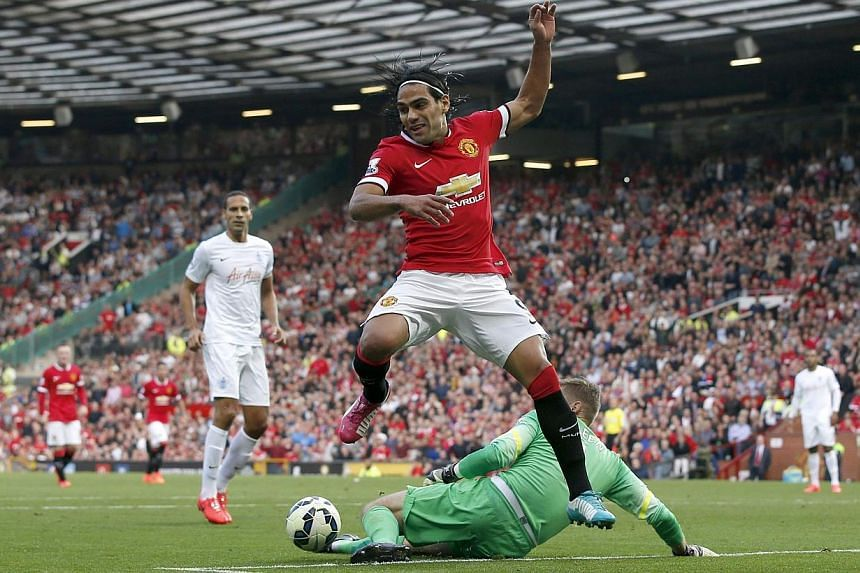 Manchester United's Radamel Falcao (front) is challenged by Queens Park Rangers' goalkeeper Robert Green (right) during their English Premier League football match at Old Trafford in Manchester, northern England on Sept 14, 2014. -- PHOTO: REUTERS