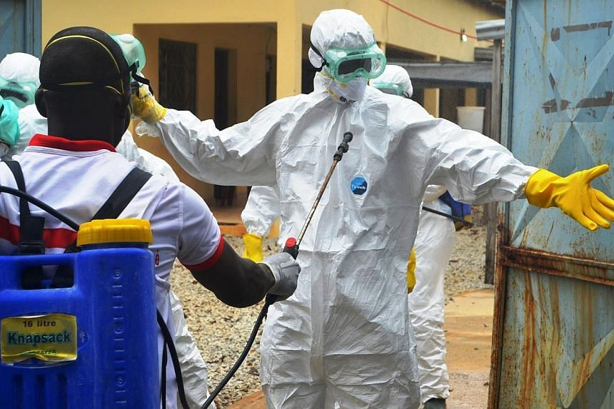 Guinea's Red Cross health workers prepare to carry the body of a victim of Ebola at an Ebola treatement centre near the hospital Donka in Conakry on Sept 14, 2014.Malaysia will send more than 20 million medical rubber gloves to five African nat