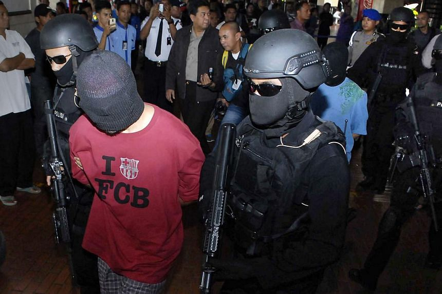 Indonesian anti-terror policemen escorting the men arrested through Jakarta airport on Sept 14, 2014. The Indonesian authorities say the suspected terrorists were trying to meet wanted militant leader Santoso, who swore allegiance to ISIS leader Abu