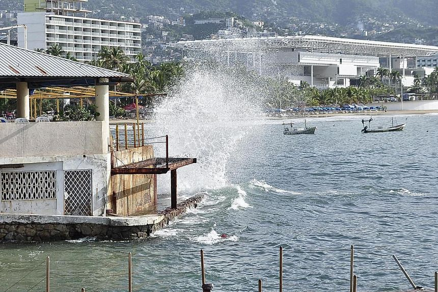 Waves pound the beach in Acapulco as Hurricane Odile churns far off shore. -- PHOTO: REUTERS