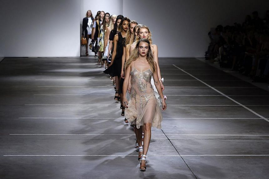 Cara Delevingne leads models in the finale of the Topshop Unique Spring/Summer 2015 collection presentation during London Fashion Week on Sept 14, 2014. -- PHOTO: REUTERS