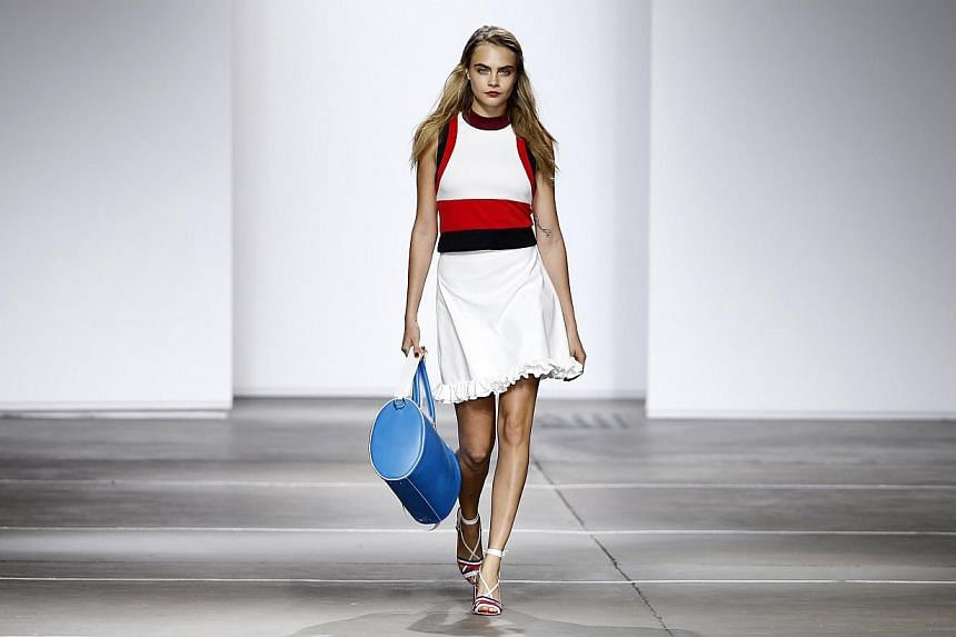Model Cara Delevingne presents a creation from the Topshop Unique Spring/Summer 2015 collection presentation during London Fashion Week on Sept 14, 2014. -- PHOTO: REUTERS