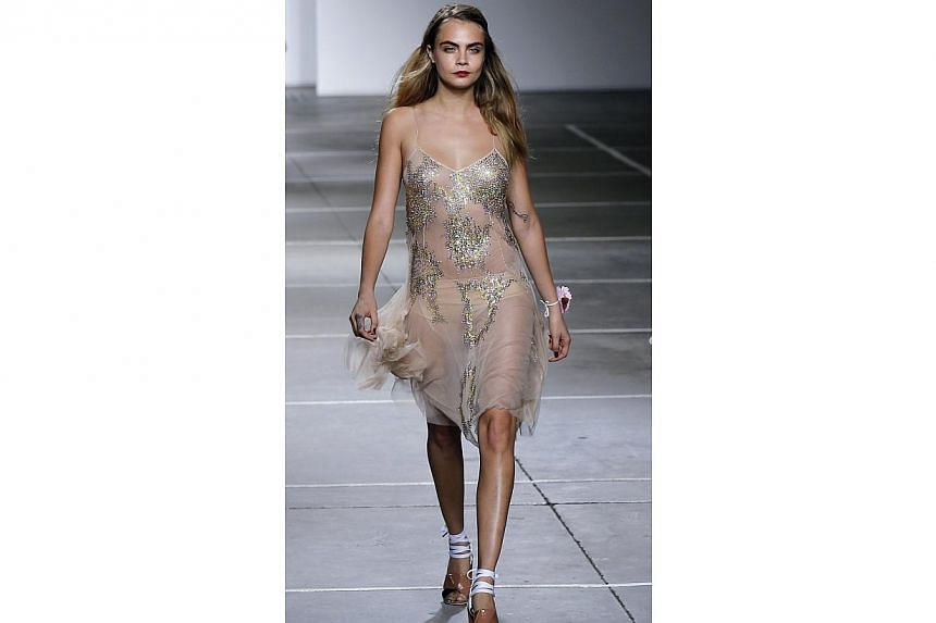 Model Cara Delevingne leaves the catwalk at the end of the Topshop Unique Spring/Summer 2015 collection presentation during London Fashion Week on Sept 14, 2014. -- PHOTO: AFP
