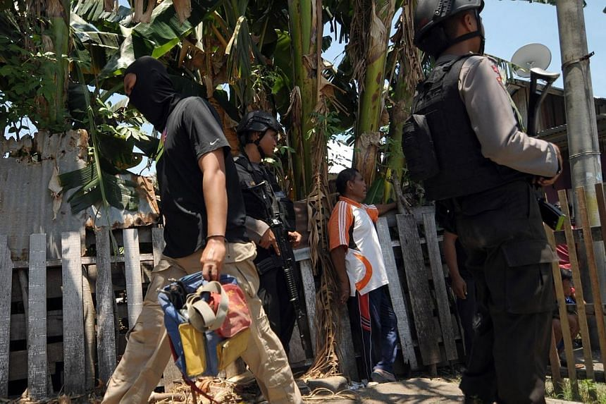 Indonesian anti-terror police Densus 88 (left) carries evidence from a house rented by terror suspects arrested in an earlier raid, in Palu on Sept 16, 2014.Indonesia's anti-terrorism police, who have arrested four Chinese Uighur jihadists link