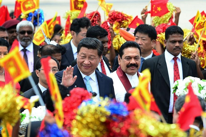 China's President Xi Jinping (centre) gestures as Sri Lankan President Mahinda Rajapakse (2nd right) looks on during a welcome ceremony at the Bandaranaike International Airport in Katunayake on Sept 16, 2014.China's President Xi Jinping held t