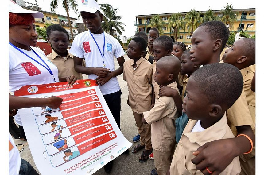 Volunteers wearing t-shirts of the United Nations Development Programme (UNDP) show a placard to raise awareness on the symptoms of the Ebola virus to students of the Sainte Therese school, in the Koumassi district, in Abidjan, on Sept 15, 2014, on t