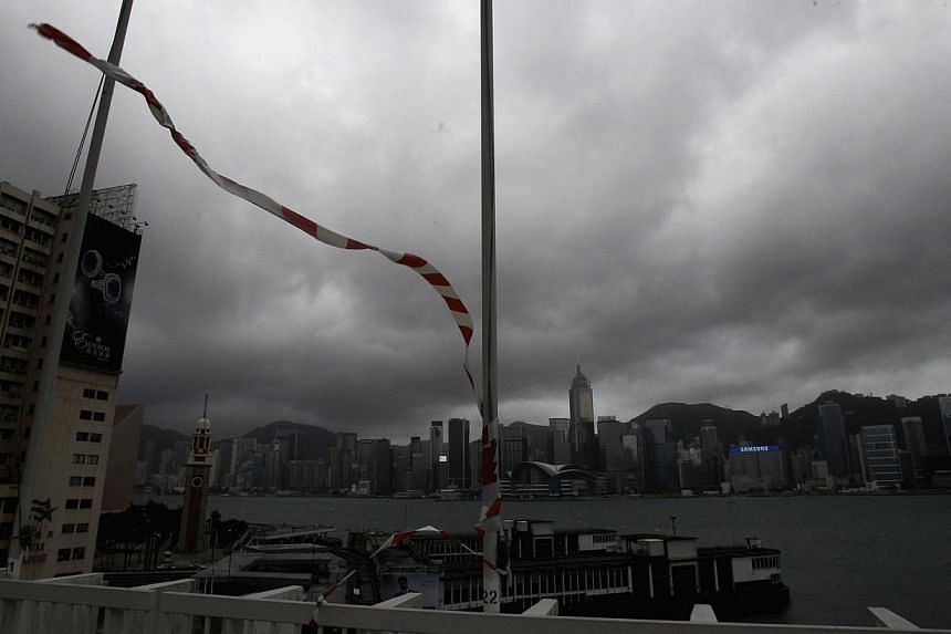 Construction tape whips about in strong winds at the Ocean Terminal, as dark clouds loom over Victoria Harbour and Hong Kong island in the background on Sept 16, 2014. -- PHOTO: REUTERS