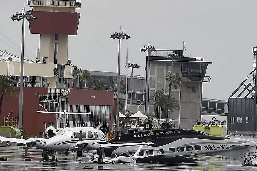 View of damaged aircrafts at the international airport of San Jose del Cabo, on Sept 15, 2014 after hurricane Odile knocked down trees and power lines in Mexico's Baja California peninsula. -- PHOTO: AFP