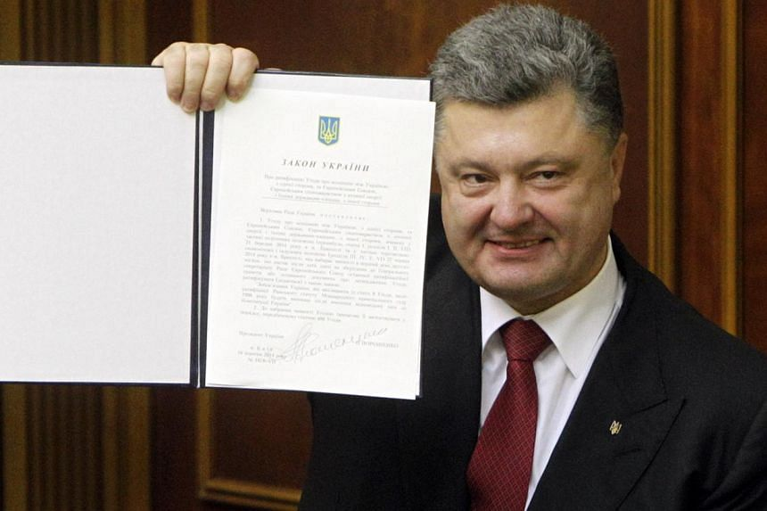 Ukraine's President Petro Poroshenko shows a signed landmark association agreement with the European Union during a session of the parliament in Kiev on Sept 16, 2014. -- PHOTO: REUTERS