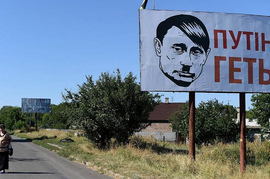 A villager walks past an Ukrainian billboard despicting Russian president Vladimir Putin bearing a Hitler moustache and haircut in Volnovakha near Donetsk, on Aug 26, 2014. Russia said on Monday that it would probe Euronews after the news channel bro