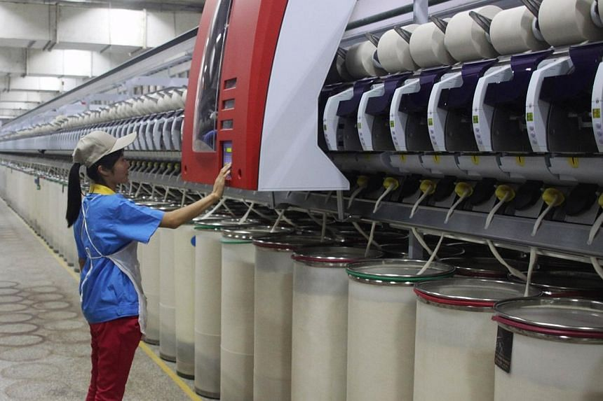"""A worker checks a control panel in a texile factory in Zouping, east China's Shandong province on Sept 16, 2014.A combination of the """"world's factory"""" and the """"world's back office"""" will drive global economic growth, Chinese President Xi Jinping"""