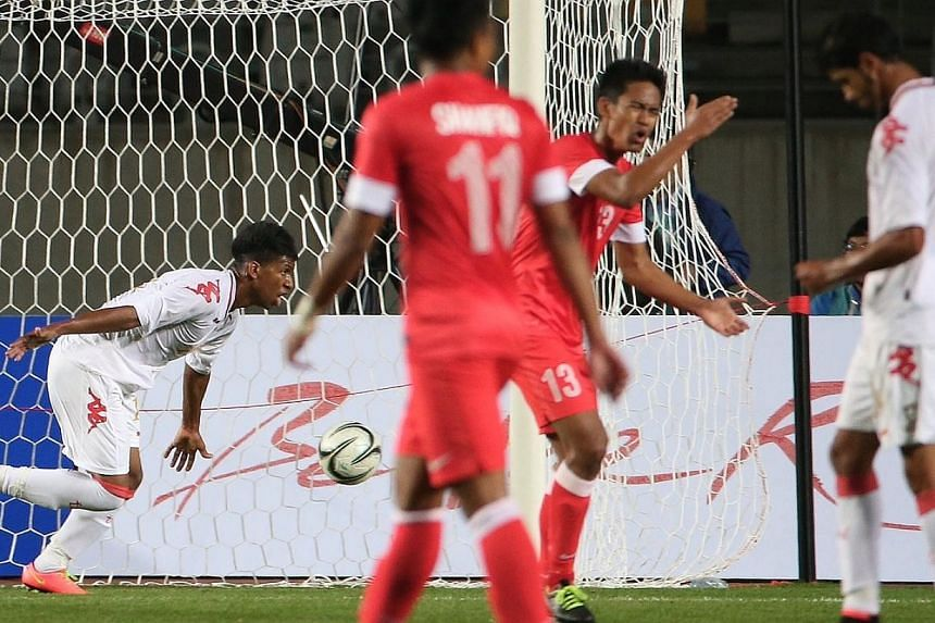 Oman's Farsi Saud Khamis Eid (extreme left) reacts after scoring Oman's third goal against Singapore during the first half of the match.-- ST PHOTO: NEO XIAOBIN
