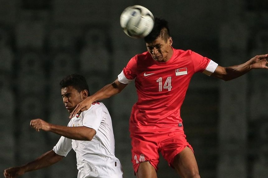Singapore's Safuwan Baharudin (right) vies for the ball with Oman's Hamhami Hatem Khamis Jamaial during the 17th Asian Games Incheon 2014 football group stage held at the Hwaseong Sports Complex Main Stadium on Sep 17, 2014.-- ST PHOTO: NEO XIA