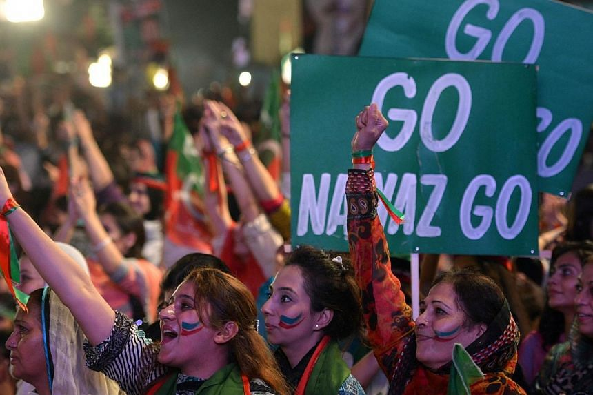 Supporters cheer for Pakistani cricketer-turned politician Imran Khan (unseen) during an anti-government protest in front of the Parliament in Islamabad on Sept 13, 2014.Anti-government protesters in Pakistan have pressed fresh murder charges a