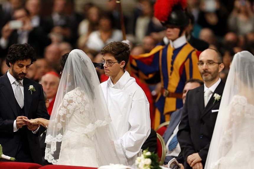 A groom exchanges rings with his bride during their wedding mass officiated by Pope Francis in St.Peter's Basilica at the Vatican, on Sept 14, 2014.Pope Francis' hopes of easing the Catholic Church's tough stance on remarried couples has hit a