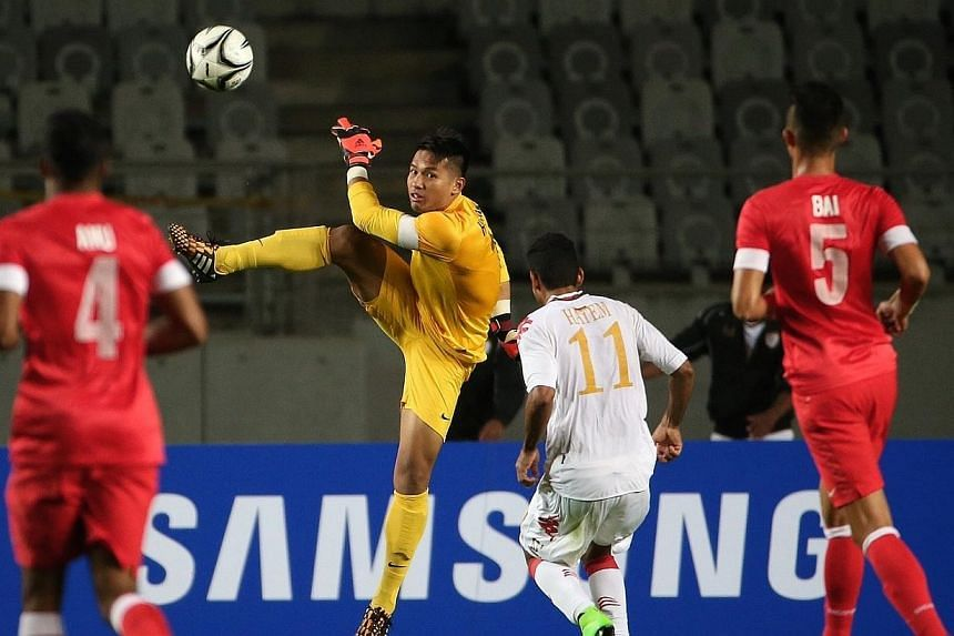 Singapore's Hassan Sunny (in yellow) clears the ball during the 17th Asian Games Incheon 2014 football group stage held at the Hwaseong Sports Complex Main Stadium on Sep 17, 2014.-- ST PHOTO: NEO XIAOBIN