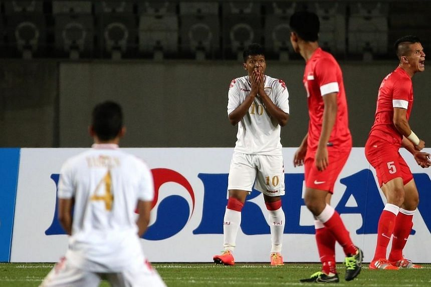 Oman's Farsi Saud Khamis Jamaial (third from right) reacts at a missed goal as Singapore's Baihakki Khaizan shouts at his team mates. -- ST PHOTO: NEO XIAOBIN
