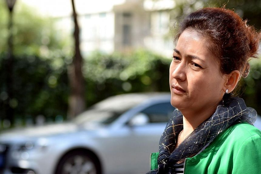 Guzaili Nuer, wife of Ilham Tohti, a former economics professor at a university in Beijing, makes her way back to the Urumqi Intermediate People's Court, as the scholar's trial resumes after a lunchbreak in Urumqi, farwest China's Xinjiang region on