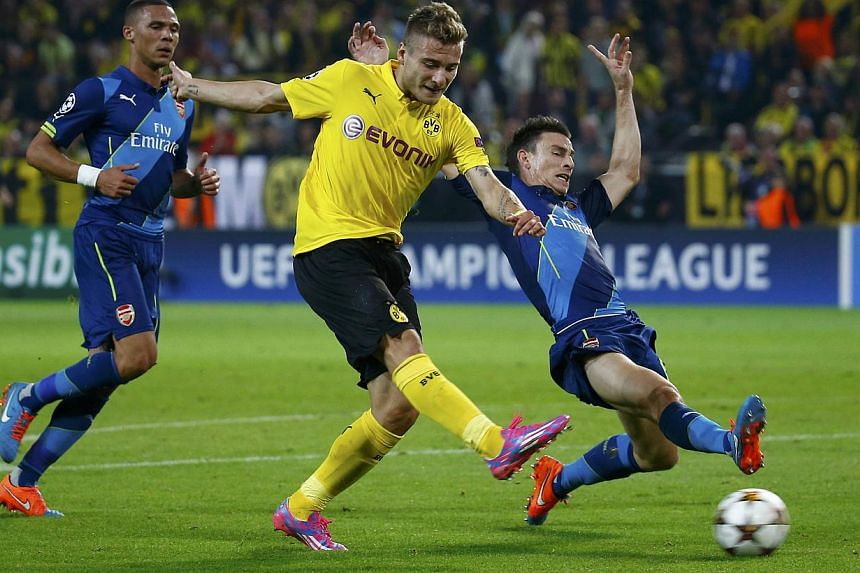 Borussia Dortmund's Ciro Immobile scores a goal past Arsenal's Laurent Koscielny (right) during their Champions League group D soccer match in Dortmund on Sept 16, 2014. -- PHOTO: REUTERS